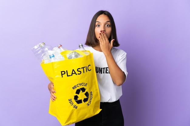 Giovane donna latina che tiene un sacchetto di riciclaggio pieno di carta da riciclare
