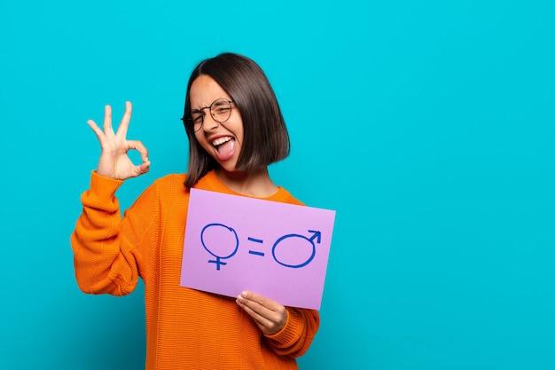 Giovane donna latina che tiene un cartello con simboli di uomo e donna. concetto di uguaglianza
