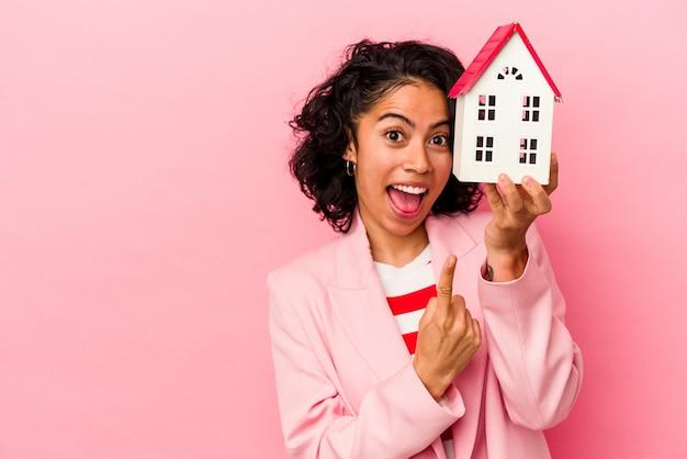 Giovane donna latina che tiene una casa giocattolo isolata su sfondo rosa che mostra il numero uno con il dito.