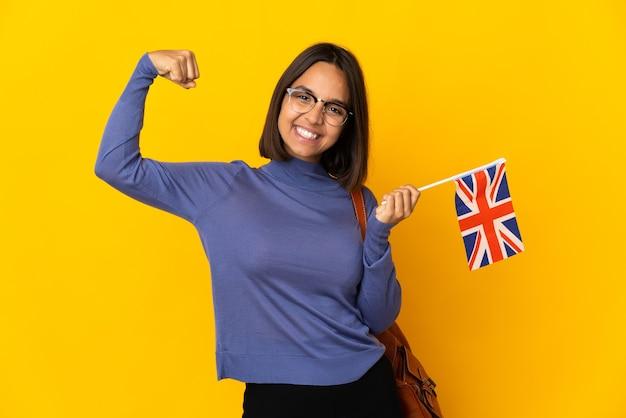 Giovane donna latina che tiene una bandiera del regno unito isolata su priorità bassa gialla che celebra una vittoria