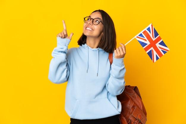 Giovane donna latina in possesso di una bandiera del regno unito isolata su sfondo giallo che indica con il dito indice una grande idea