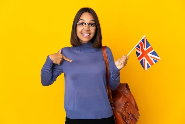 Giovane donna latina che tiene una bandiera del regno unito isolata su priorità bassa gialla con l'espressione facciale di sorpresa
