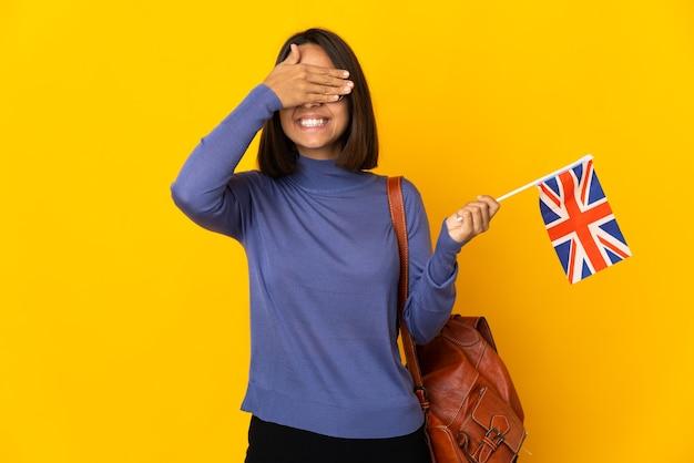 Giovane donna latina che tiene una bandiera del regno unito isolata sul muro giallo che copre gli occhi con le mani e sorridente