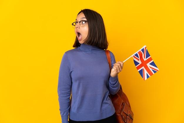 Giovane donna latina che tiene una bandiera del regno unito isolata sulla parete gialla che fa gesto di sorpresa mentre guarda al lato