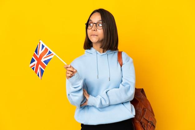 Giovane donna latina che tiene una bandiera del regno unito isolata sulla parete gialla che ha dubbi mentre guarda lato