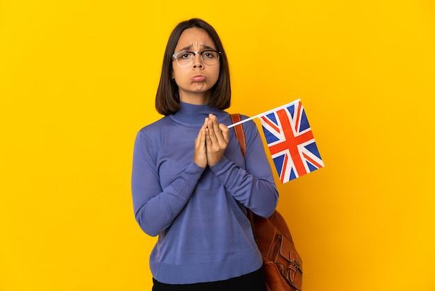 La giovane donna latina che tiene una bandiera del regno unito isolata sulla parete gialla tiene insieme la palma. la persona chiede qualcosa