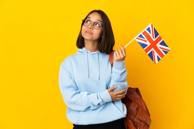 Giovane donna latina che tiene una bandiera del regno unito isolata sulla parete gialla che osserva in su mentre sorride