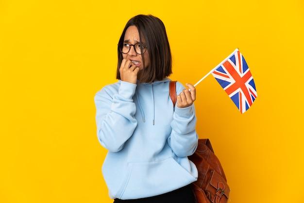 Giovane donna latina che tiene una bandiera del regno unito isolata sulla parete gialla nervosa e spaventata