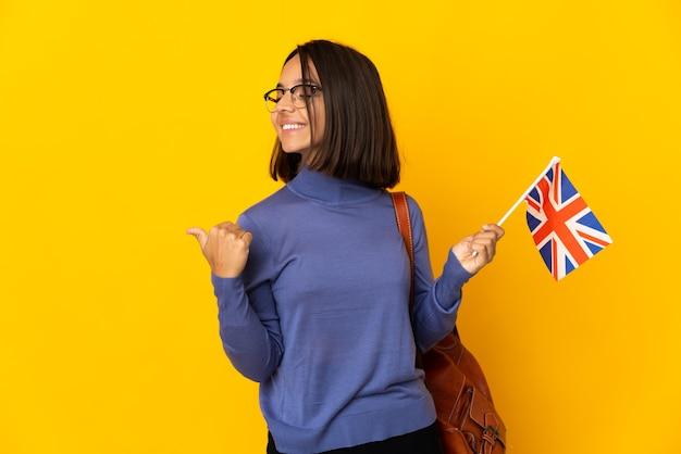 Giovane donna latina che tiene una bandiera del regno unito isolata sulla parete gialla che indica al lato per presentare un prodotto