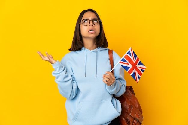 La giovane donna latina che tiene una bandiera del regno unito isolata sulla parete gialla ha sottolineato sopraffatto
