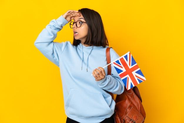Giovane donna latina che tiene una bandiera del regno unito isolata sulla parete gialla con l'espressione di sorpresa mentre guarda il lato