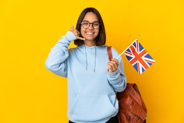Giovane donna latina che tiene una bandiera del regno unito isolata