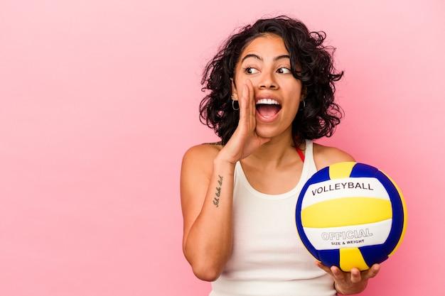 La giovane donna latina che tiene una palla da pallavolo isolata su fondo rosa sta dicendo un segreto