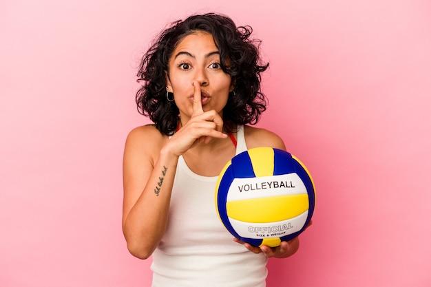 Giovane donna latina in possesso di una palla da pallavolo isolata su sfondo rosa mantenendo un segreto