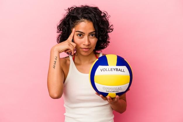 Giovane donna latina che tiene una palla da pallavolo isolata su sfondo rosa che punta il tempio con il dito