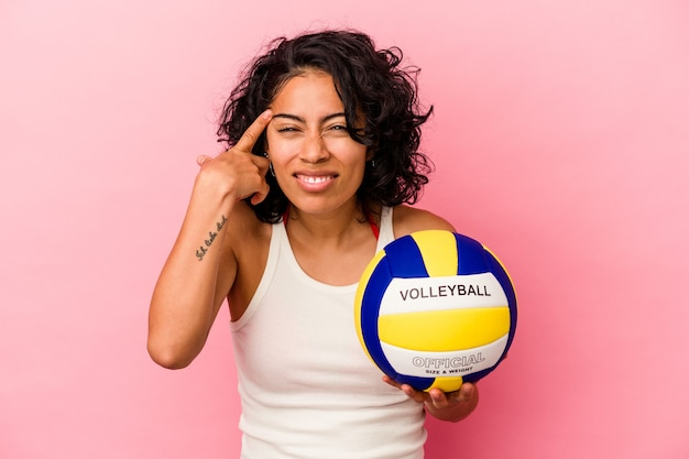 Giovane donna latina in possesso di una palla da pallavolo isolata su sfondo rosa che mostra un gesto di delusione