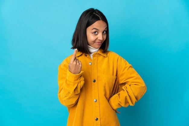 Giovane donna latina isolata su sfondo blu che fa gesto imminente