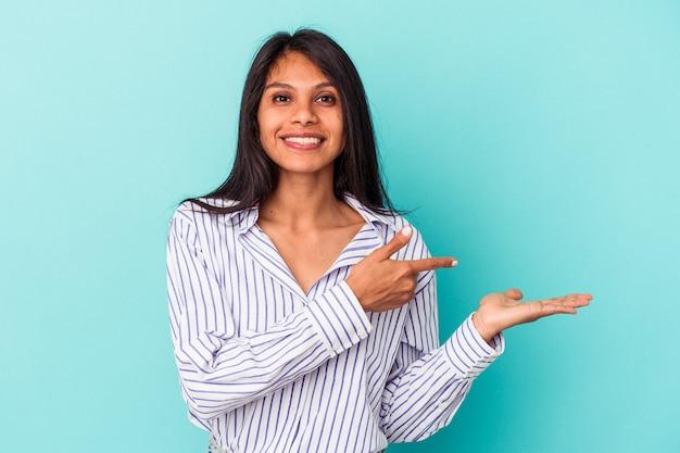 Giovane donna latina isolata su sfondo blu eccitata in possesso di uno spazio di copia sul palmo.