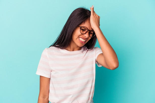 Giovane donna latina isolata su sfondo blu dimenticando qualcosa, schiaffeggiando la fronte con il palmo e chiudendo gli occhi.