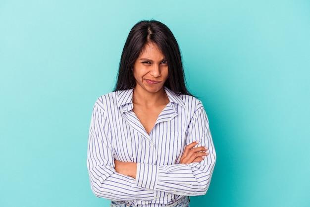 La giovane donna latina isolata sul fronte blu accigliato nel dispiacere, tiene le braccia conserte.
