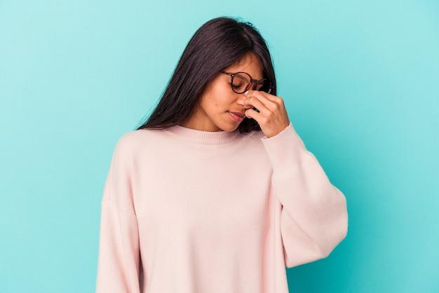 Giovane donna latina isolata su sfondo blu che ha mal di testa, toccando la parte anteriore del viso.