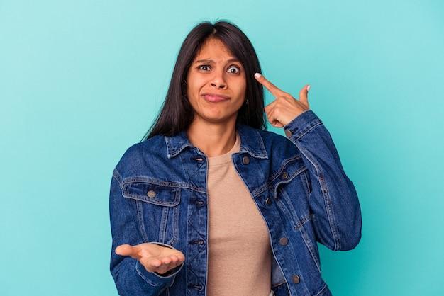 Giovane donna latina isolata su sfondo blu che tiene e mostra un prodotto a portata di mano.