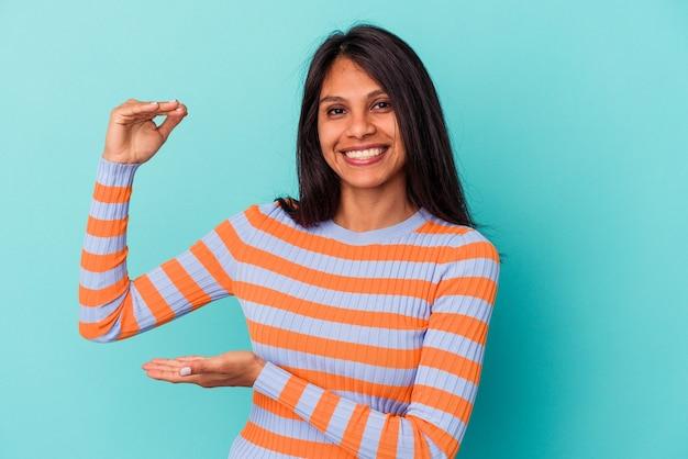 Giovane donna latina isolata su sfondo blu che tiene qualcosa di piccolo con l'indice, sorridente e fiducioso.