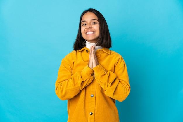 La giovane donna latina isolata su priorità bassa blu tiene insieme la palma. la persona chiede qualcosa