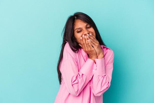 Giovane donna latina isolata su sfondo blu che ride di qualcosa, coprendo la bocca con le mani.
