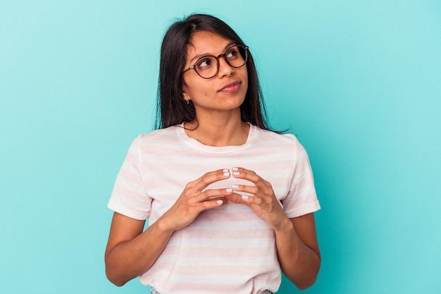 Giovane donna latina isolata su sfondo blu che compone piano in mente, la creazione di un'idea.