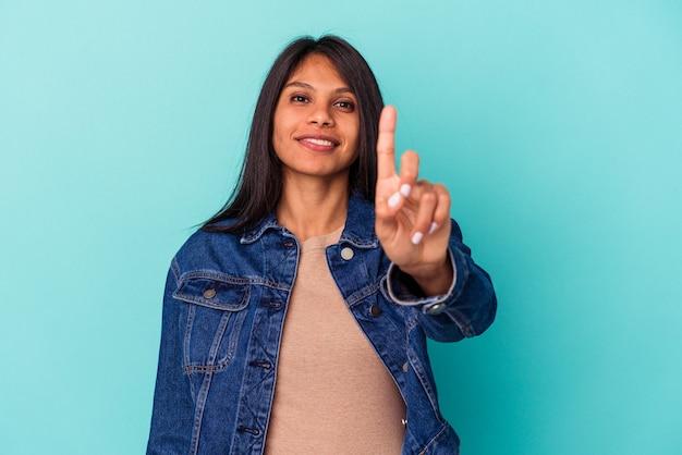 Giovane donna latina isolata su sfondo blu che mostra il numero uno con il dito.