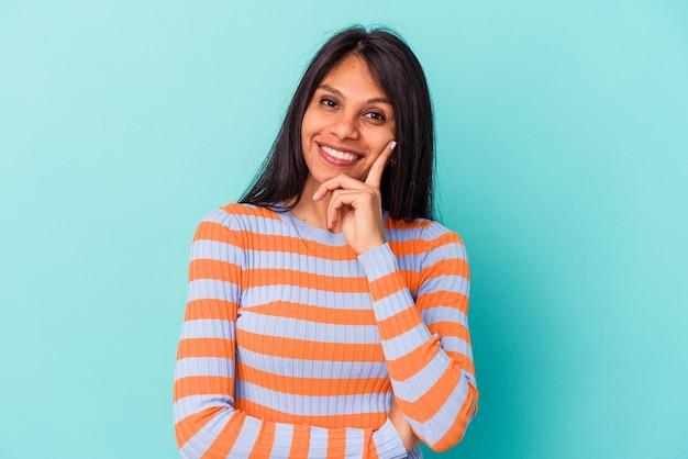 Giovane donna latina isolata su sfondo blu sorridente felice e fiducioso, toccando il mento con la mano.