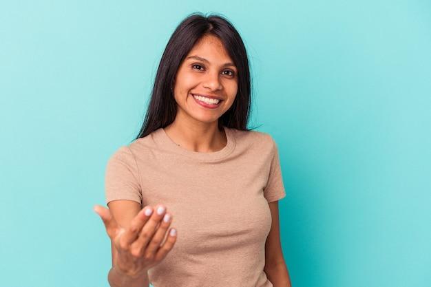 Giovane donna latina isolata su fondo blu che allunga la mano alla macchina fotografica nel gesto di saluto.