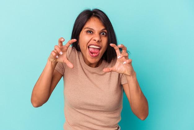 Giovane donna latina isolata su sfondo blu sconvolto urlando con le mani tese.