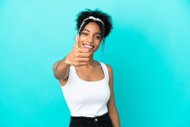Giovane donna latina isolata su sfondo blu con il pollice in alto perché è successo qualcosa di buono