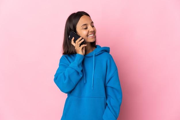 Giovane donna latina isolata mantenendo una conversazione con il telefono cellulare con qualcuno