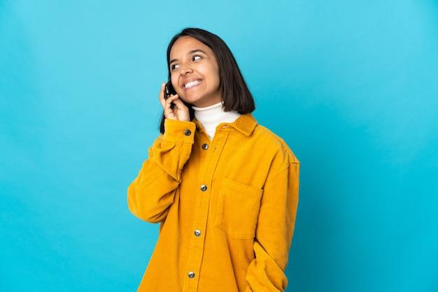 Giovane donna latina isolata mantenendo una conversazione con il telefono cellulare