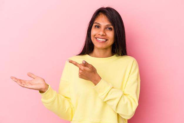 Giovane donna latina isolata su sfondo rosa eccitata tenendo in mano uno spazio di copia sul palmo.