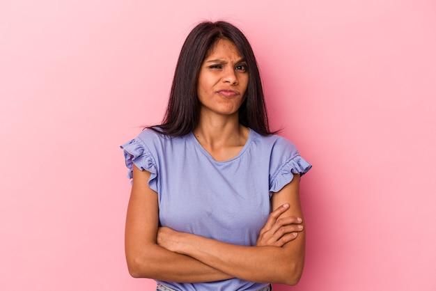 La giovane donna latina isolata sul fronte rosa accigliato nel dispiacere, tiene le braccia conserte.