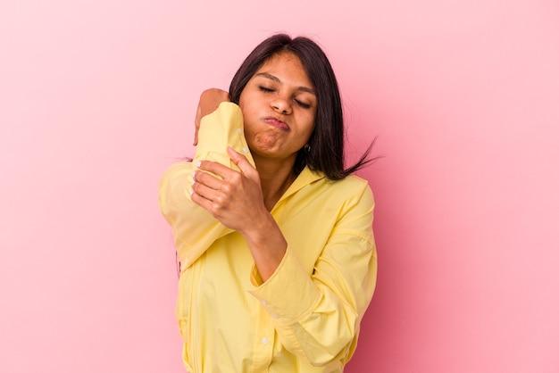 Giovane donna latina isolata su sfondo rosa con dolore al collo dovuto allo stress, massaggiandolo e toccandolo con la mano.