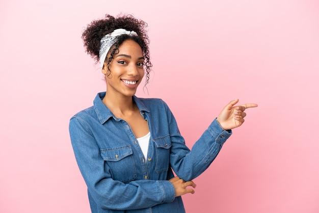 Giovane donna latina isolata su sfondo rosa che punta il dito a lato