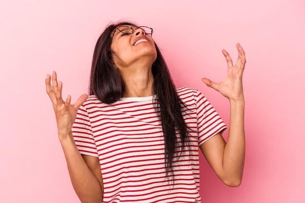 Giovane donna latina isolata su sfondo rosa che urla al cielo, alzando lo sguardo, frustrata.