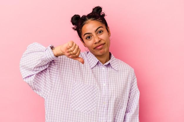 Giovane donna latina isolata su sfondo rosa che mostra un gesto di antipatia, pollice verso. concetto di disaccordo.