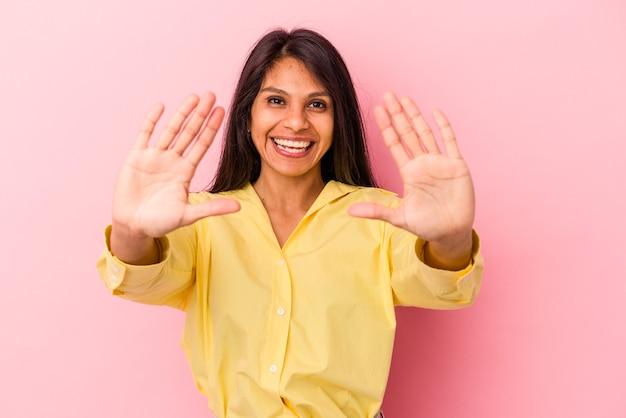 Giovane donna latina isolata su sfondo rosa che mostra il numero dieci con le mani.
