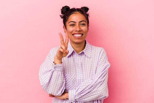 Giovane donna latina isolata su sfondo rosa che mostra il numero due con le dita.
