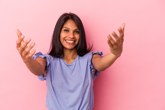 Giovane donna latina isolata su sfondo rosa che mostra un'espressione di benvenuto.