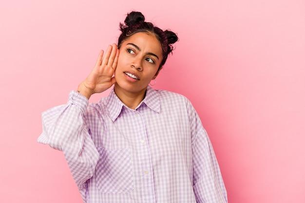 Giovane donna latina isolata su sfondo rosa cercando di ascoltare un pettegolezzo.