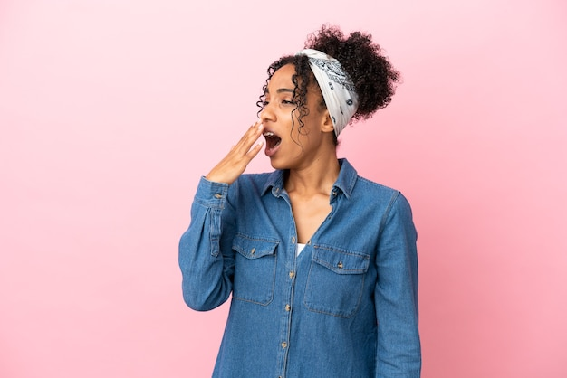 Giovane donna latina isolata su sfondo rosa che sbadiglia e copre la bocca spalancata con la mano