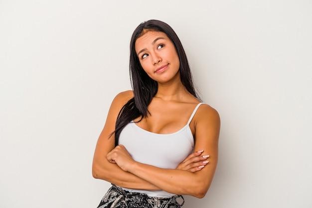Giovane donna latina isolata su sfondo bianco che sogna di raggiungere obiettivi e scopi
