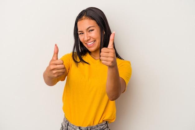 Giovane donna latina isolata su sfondo bianco alzando entrambi i pollici, sorridente e fiducioso.